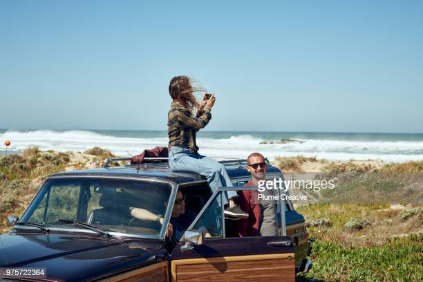Woman taking photo of beach from roof of car