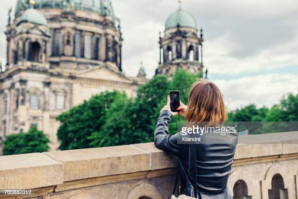 Woman taking photo of Berlin Cathedral with mobile phone