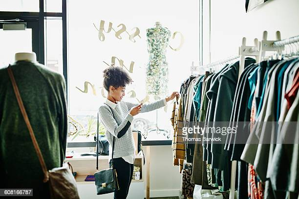 woman taking photo of clothing with smartphone - consumentisme stockfoto's en -beelden