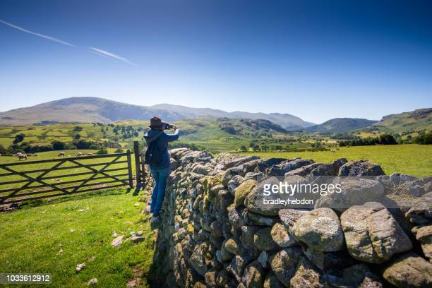 Woman taking photo of countryside near Keswick, England