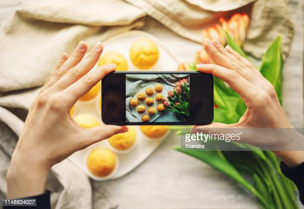 woman taking photo of cupcakes with smartphone - influencer photos stock photos and pictures