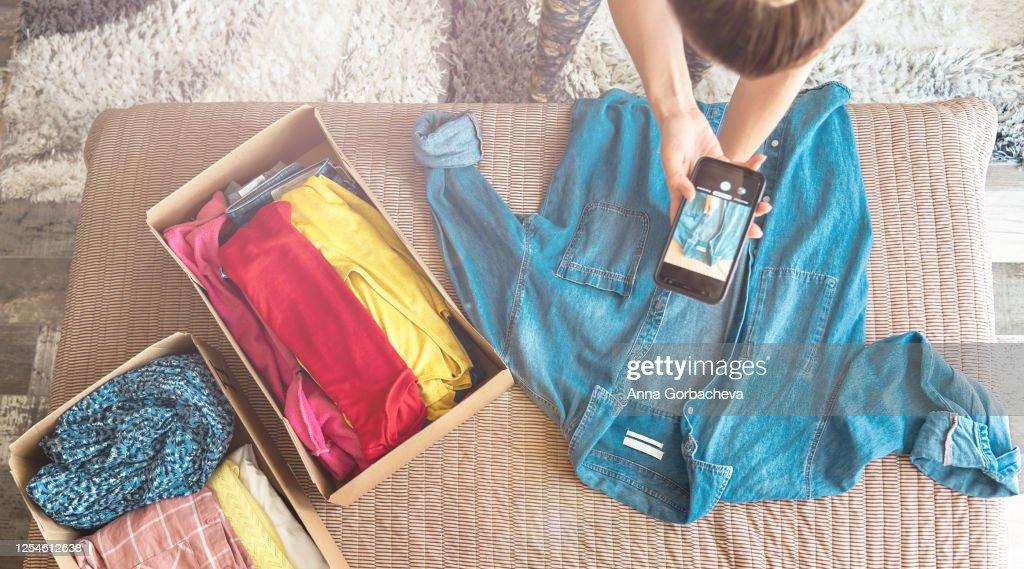 Vrouw die foto van denimshirt op smartphone neemt om het op internetwinkel te verkopen. : Stockfoto