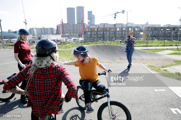 woman taking photo of female friends with bikes - bmx track london stock pictures, royalty-free photos & images