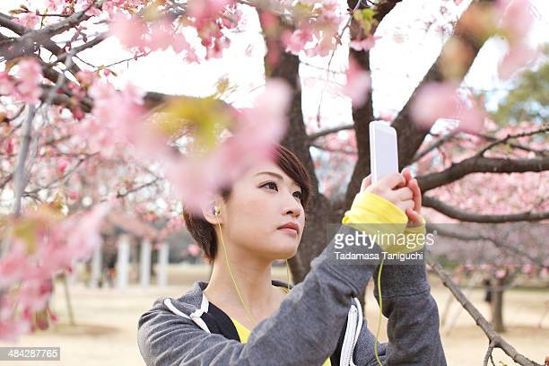 Woman taking photo of flower