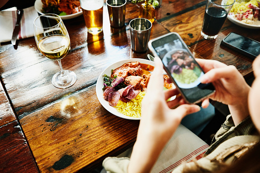 Woman taking photo of food with smartphone while having lunch with friends in restaurant - gettyimageskorea