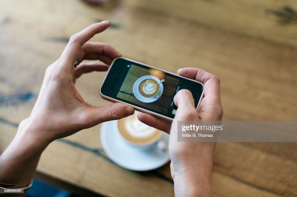 Woman Taking Photo Of Her Coffee At A Cafe : Stock Photo