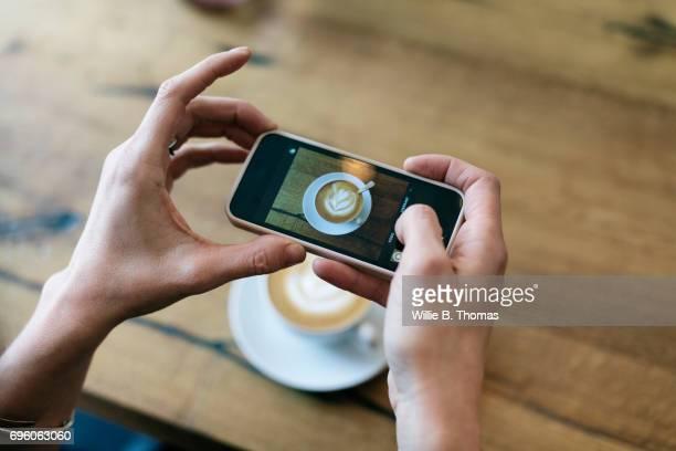 woman taking photo of her coffee at a cafe - b fotos - fotografias e filmes do acervo