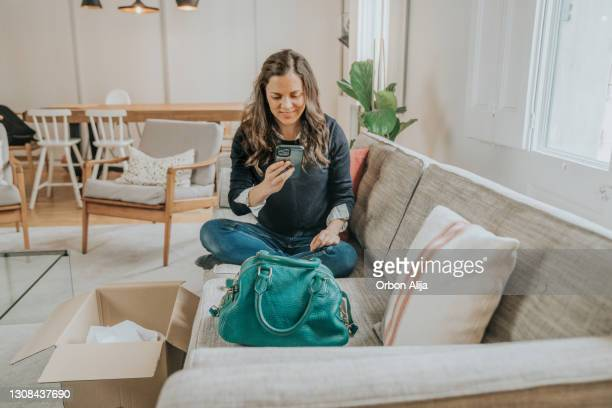 woman taking photo of her new brand purse - clutch bag stock pictures, royalty-free photos & images