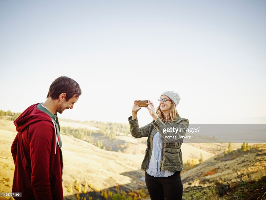 Woman taking photo of husband with smart phone : Stock Photo