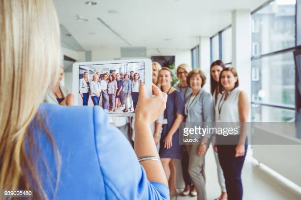 Woman taking photo of large group of happy women, using digital tablet