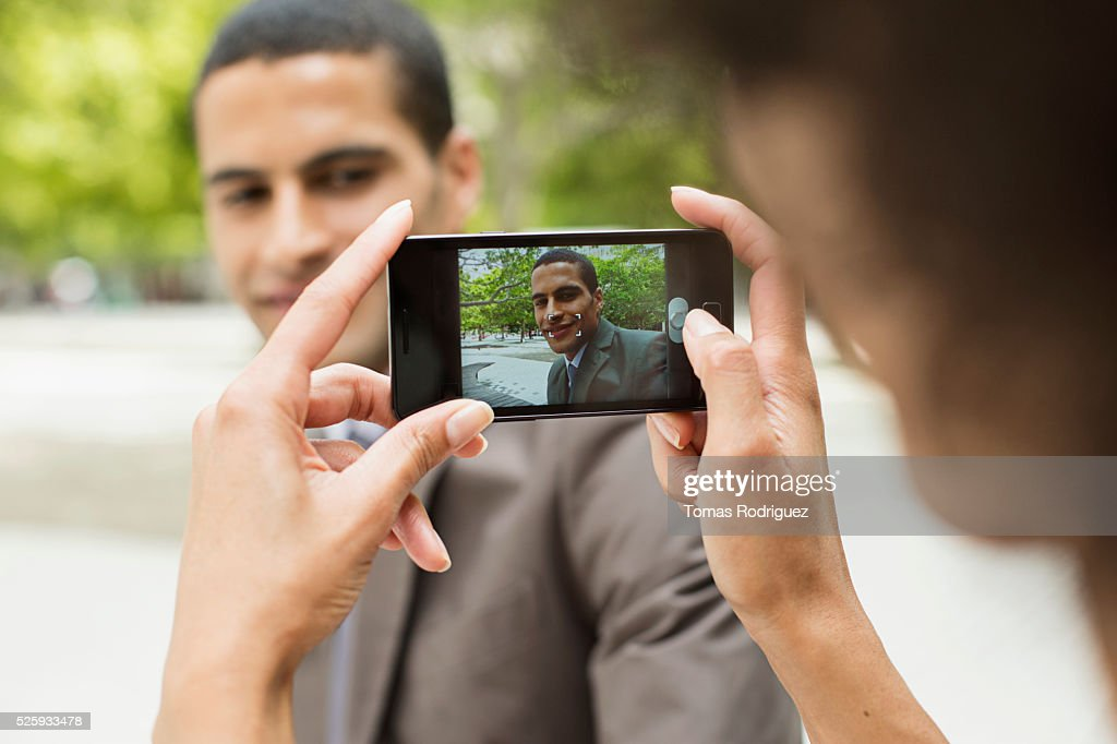 Woman taking photo of man with cell phone : Stock Photo