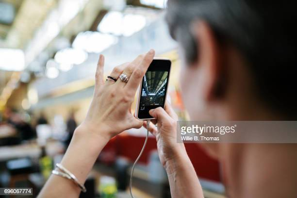 Woman Taking Photo Of Market With Smartphone