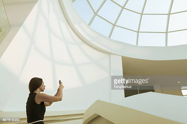 Woman taking photo of modern skylight in atrium