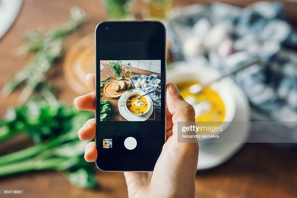 Woman taking photo of pumpkin soup with smartphone : Stock Photo