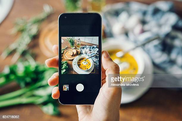 woman taking photo of pumpkin soup with smartphone - photography stockfoto's en -beelden