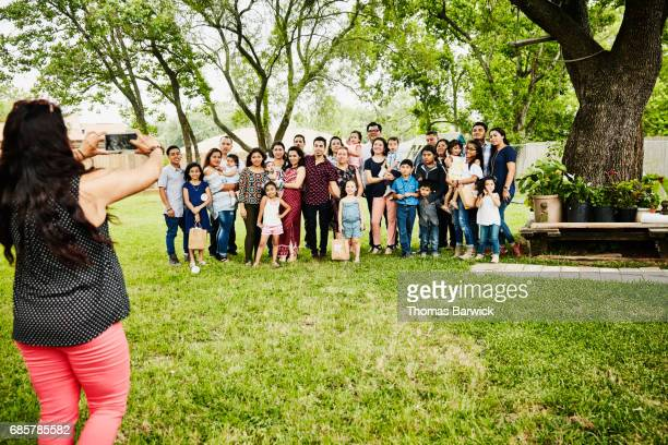 woman taking photo of smiling multigenerational family gather for backyard birthday party - family reunion stock pictures, royalty-free photos & images