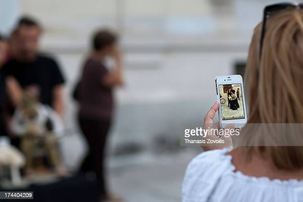 Woman taking photo with a mobile phone of a street performers in Athens, Greece.