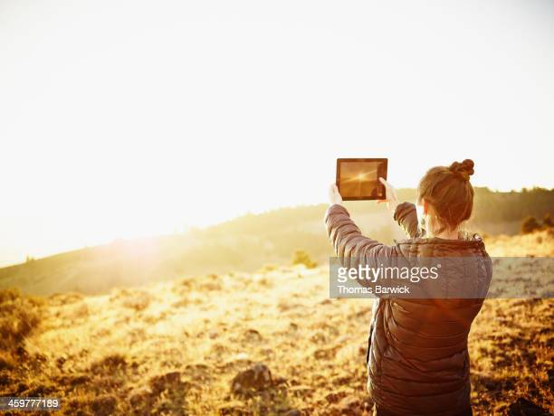 Woman taking photo with digital tablet at sunset