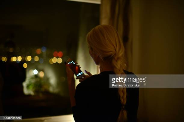 Woman taking photo with her mobile phone through a window at night