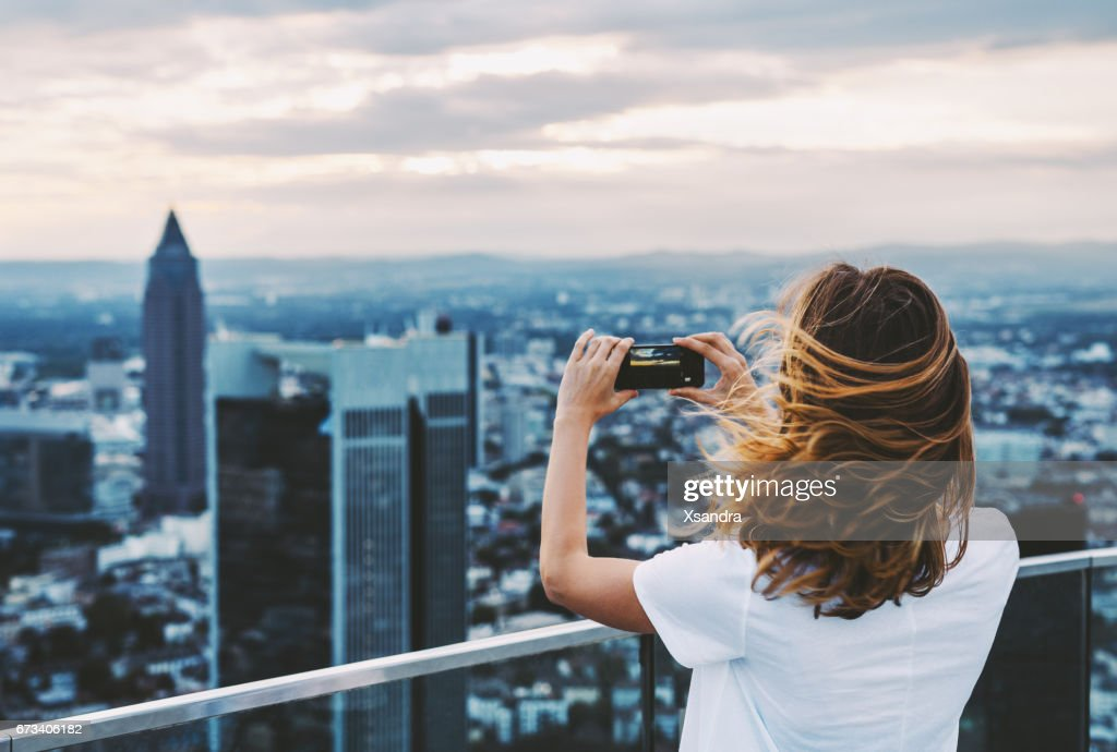 Woman taking photo with mobile phone above city : Stock Photo