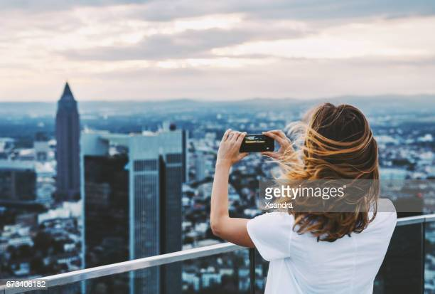Woman taking photo with mobile phone above city