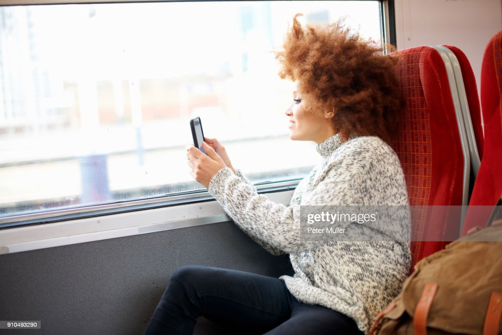 Woman taking photo with mobile phone from train, London : Stock Photo