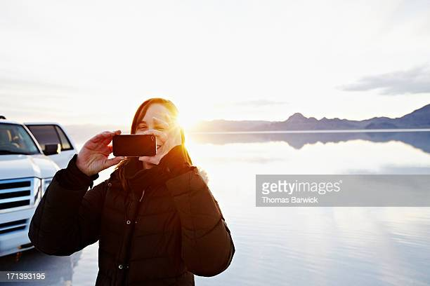 Woman taking photo with smartphone at sunset