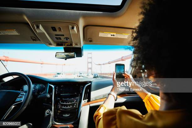 Woman taking photo with smartphone while riding in car across Golden Gate Bridge