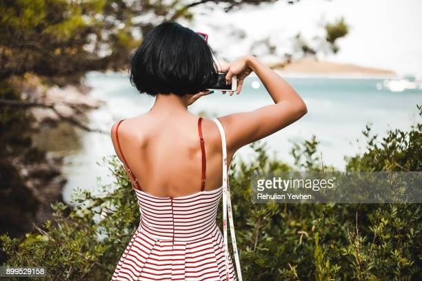 Woman taking photograph of coast, Koralat, Zagrebacka, Croatia