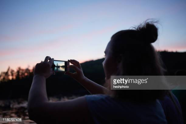 woman taking photograph of sunset with smartphone - heshphoto stockfoto's en -beelden