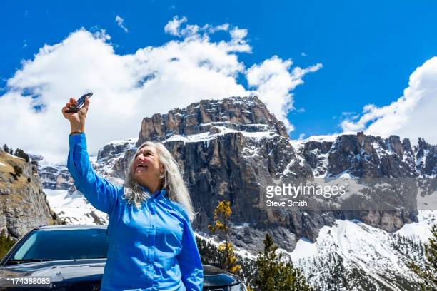 woman taking photograph with smart phone by mountain in dolomites, italy - カナツェイ ストックフォトと画像