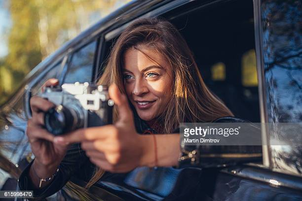 Woman taking photos from the car window