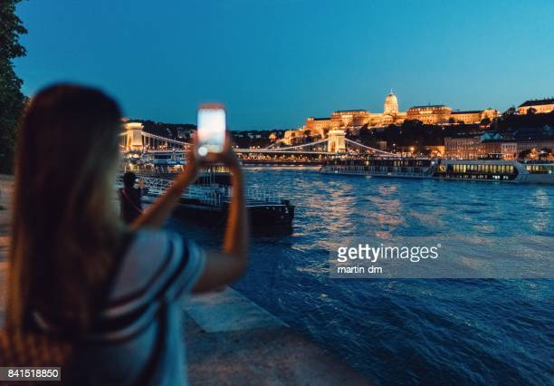 Woman taking photos of Budapest city at night