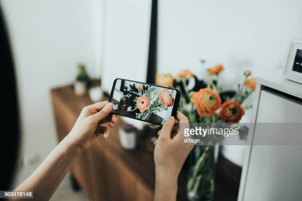 Woman taking photos of flowers with mobile phone