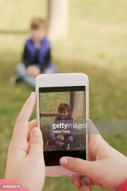 Woman taking photos of her son at garden