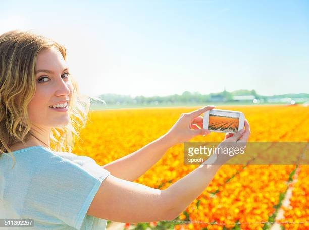 Woman taking photos of tulip field in Netherlands
