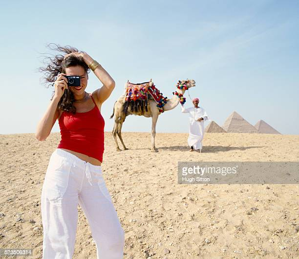 woman taking picture and man with camel - hugh sitton imagens e fotografias de stock