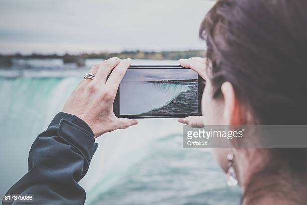 woman taking picture at niagara falls with smart phone - niagara falls photos stock photos and pictures