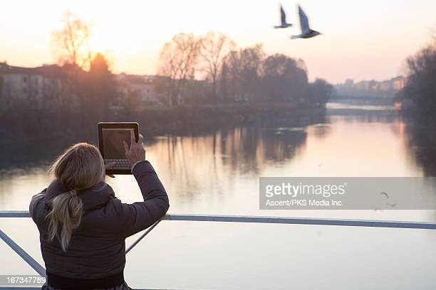 Woman taking picture from bridge