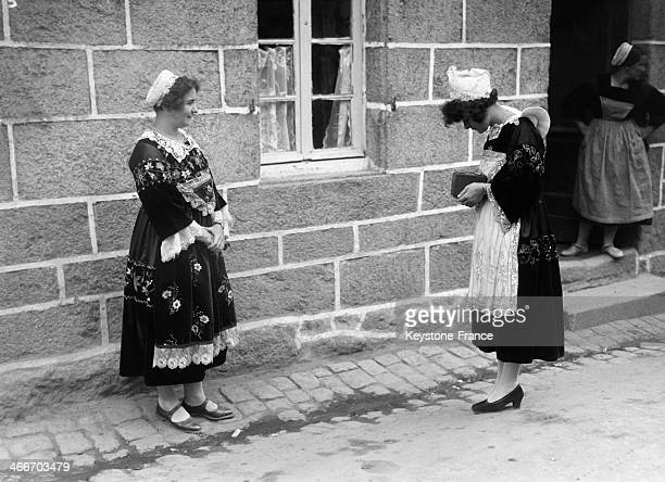 Woman taking picture of a friend wearing a traditional Britton costume during the Celtic festival in August 1929 in Huelgoat France