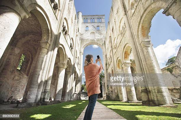 Woman taking picture of cathedral ruins