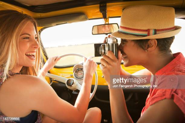 Woman taking picture of friend driving old-fashioned car
