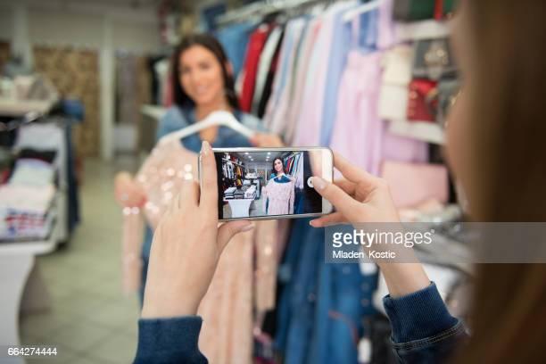 Vrouw nemen foto van haar vriendin in kledingwinkel