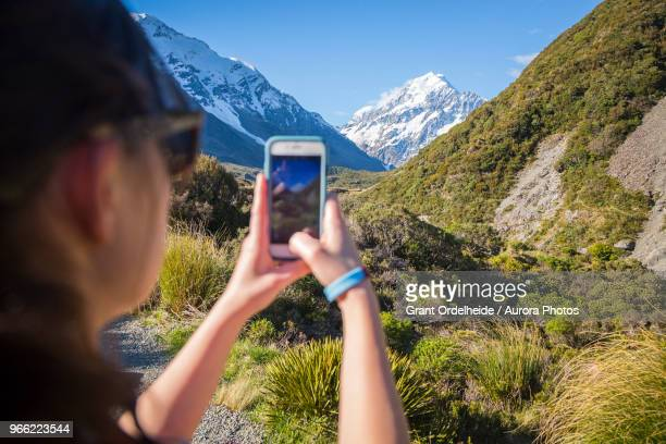 Woman taking picture of Mount Cook, Hooker Valley Track, Canterbury, New Zealand