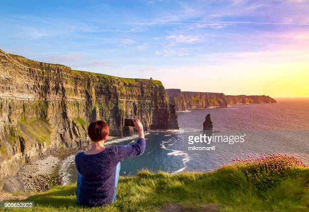 Woman taking picture of Of Cliffs Of Moher, Liscannor, Ireland