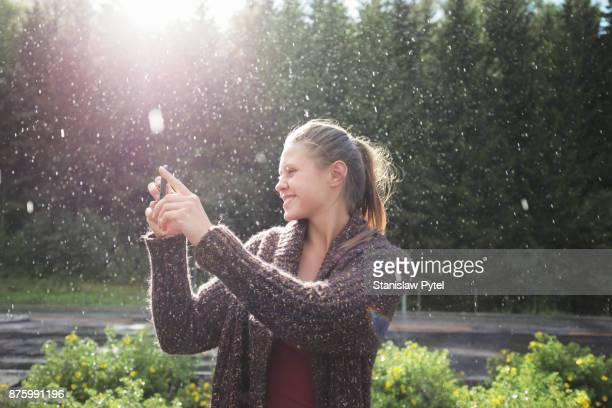 Woman taking picture of rain and sun, smiling