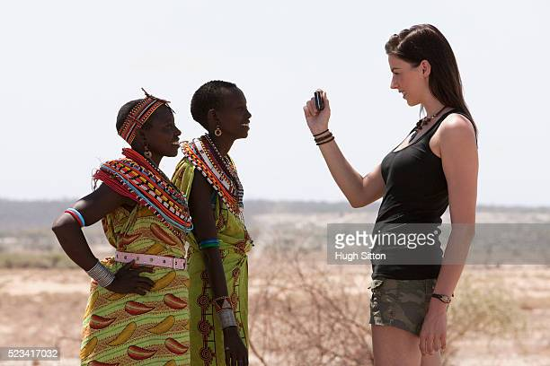 woman taking picture of tribespeople - hugh sitton stock pictures, royalty-free photos & images