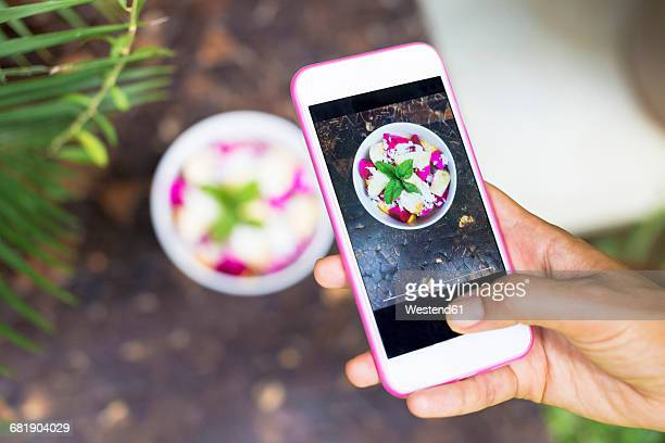 Woman taking picture of tropical fruit salad with cell phone, close-up
