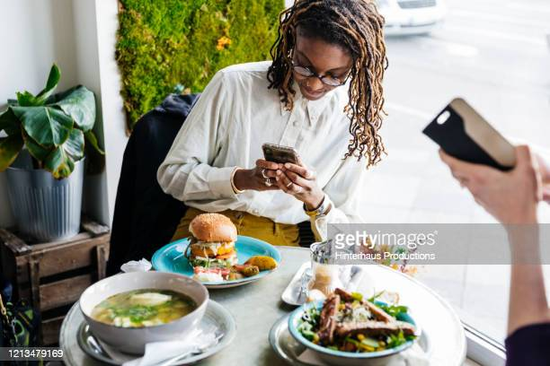 woman taking picture of vegan meal with smartphone - fotohandy stock-fotos und bilder