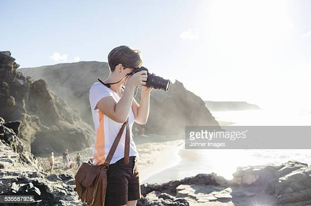 Woman taking picture on beach